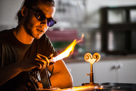 Glassblowing Professional Working on a Torch Flame with Glass Tubes