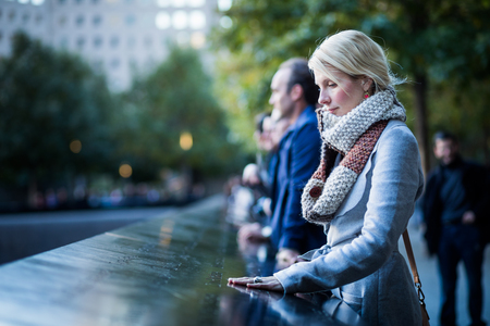 NEW YORK, USA. Sad woman looking at the Names of World Trade Center Memorial