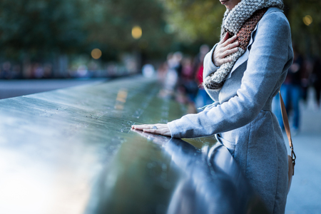 NEW YORK, USA. Sad woman looking at the Names of World Trade Center Memorial