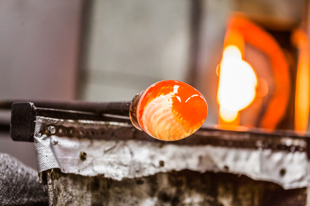 Glassblowing Spinning Piece and Furnace in Background Stock Photo