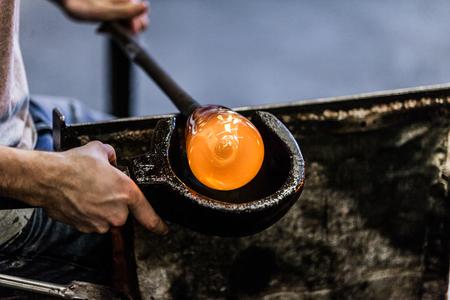 Man Hands Closeup Shaping a Blown Glass Piece with a Wooden Block Stockfoto
