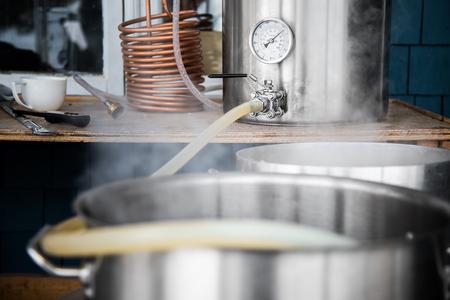 Equipo de preparación casera y verter la hierba de cerveza artesanal en la caldera hervir con un tubo de silicona. Foto de archivo - 82264282