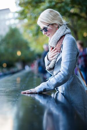 14: NEW YORK, USA - October 14, 2016. Sad woman looking at the Names of World Trade Center Memorial Editorial