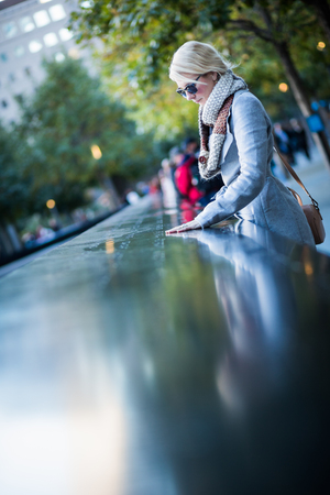 NEW YORK, USA - October 14, 2016. Sad woman looking at the Names of World Trade Center Memorial Editorial