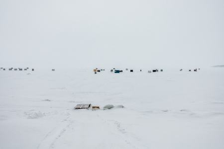 frozen lake: Miguasha, Canada - February 16, 2017. Ice Smelt Fishing Shack during a Freezing and Windy Day of Winter in Quebec