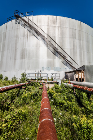 Big Abandoned Oil Refinery Gas Tank and Rusty Pipeline Stock Photo