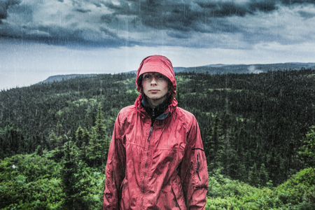 Unpredictable Heavy Rain Pouring on a Sad and Frustrated Young Woman Alone on top of a Mountain. Archivio Fotografico