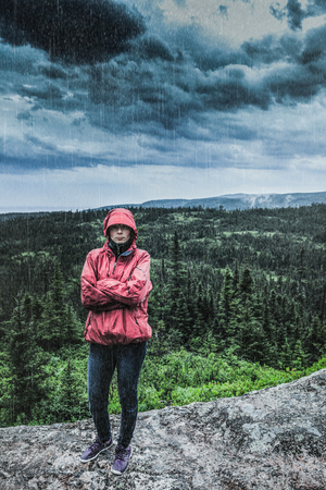Unpredictable Heavy Rain Pouring on a Sad and Frustrated Young Woman Alone on top of a Mountain. Stock Photo