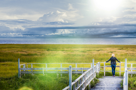 Lonely Young Woman Looking at the Amazing Calm Landscape from a Wood Balcony. Stock Photo