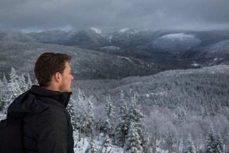 Young Man Alone on top of Mountain during Winter