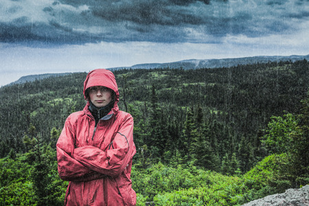 Unpredictable Heavy Rain Pouring on a Sad and Frustrated Young Woman Alone on top of a Mountain. Stockfoto