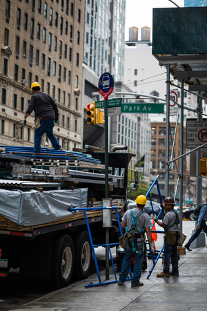 NEW YORK, USA - October 13, 2016. Few People Unloading Truck  with Construction Materials like Scaffolds and other Structure on 5th Avenue, New York.