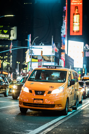 NEW YORK, USA - October 14, 2016. Traffic and Yellow Hybrid Cabs in Times Square at Night, Manhattan, New York.
