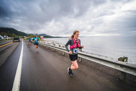 CARLETON, CANADA - 4 juin 2017. Pendant le 5e marathon de Carleton au Québec, Canada. Jeune femme marathonienne menant du côté de la route et de l'océan Banque d'images - 82386353