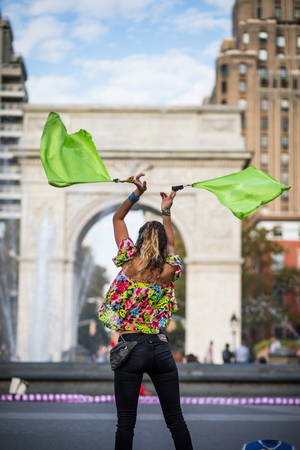 NEW YORK, USA - October 17, 2016. Woman Juggling with Flags, in the Middle of Washington Square Park, Greenwich Park in New York City.
