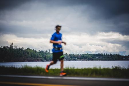CARLETON, CANADA - 4 juin 2017. Au cours du 5e Marathon de Carleton au Québec, au Canada. Young Blurry Man Marathoner à environ 7 km de distance Seul sur le coté de la route et de l'océan Banque d'images - 82386381