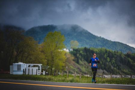 CARLETON, CANADA - 4 juin 2017. Au cours du 5e Marathon de Carleton au Québec, au Canada. Jeune femme Marathoner à environ 7 km de distance Seul sur le coté de la route et de l'océan Banque d'images - 82386388