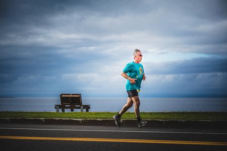CARLETON, CANADA - 4 juin 2017. Au cours du 5e Marathon de Carleton au Québec, au Canada. Un homme âgé qui court seul pendant le Marathon avec le magnifique paysage de l'océan. Banque d'images - 82386402