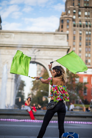 show window: NEW YORK, USA - October 17, 2016. Woman Juggling with Flags, in the Middle of Washington Square Park, Greenwich Park in New York City.