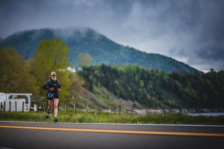 CARLETON, CANADA - 4 juin 2017. Au cours du 5e Marathon de Carleton au Québec, au Canada. Marathoner senior seul sur le bord de la route et de l'océan. Banque d'images - 82386416