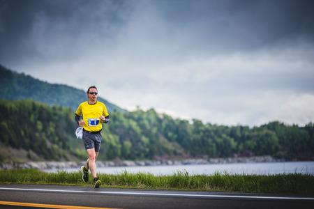 CARLETON, CANADA - 4 juin 2017. Au cours du 5e Marathon de Carleton au Québec, au Canada. Young Marathoner seul au bord de la route et de l'océan Banque d'images - 82386451