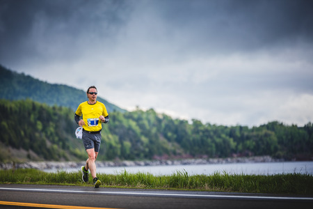 CARLETON, CANADA - June 4, 2017. During the 5th Marathon of Carleton in Quebec, Canada. Young Marathoner Alone on the side of the Road and Ocean