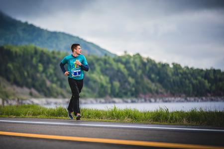 CARLETON, CANADA - 4 juin 2017. Au cours du 5e Marathon de Carleton au Québec, au Canada. Young Marathoner seul au bord de la route et de l'océan Banque d'images - 82386457