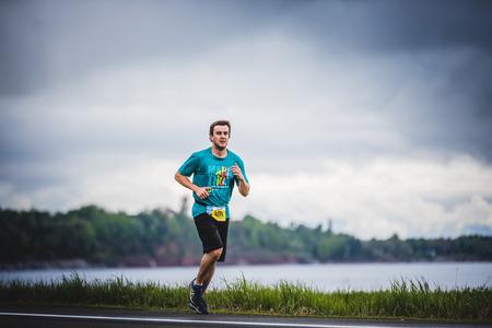 CARLETON, CANADA - 4 juin 2017. Au cours du 5e Marathon de Carleton au Québec, au Canada. Young Man Marathoner à environ 7 km de distance Seul sur le coté de la route et de l'océan Banque d'images - 82386474