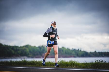 CARLETON, CANADA - 4 juin 2017. Au cours du 5e Marathon de Carleton au Québec, au Canada. Marathoner senior seul sur le bord de la route et de l'océan. Banque d'images - 82386483