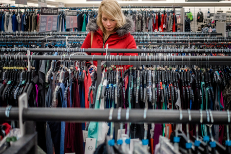clothing store: RIMOUSKI, CANADA - February 19, 2017. Woman Looking for Deals in a Winners Store in Rimouski, Quebec. Editorial