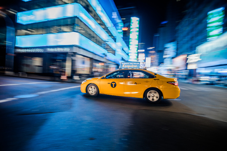 NEW YORK, USA - October 17, 2016. NYC Yellow Cab passing Fast at Night in Timesquare Manhattan, New York.