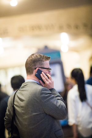 NEW YORK, USA - October 18, 2016. Businessman Traveling and on the Phone in the Grand Central Subway Station in Manhattan on a buzy Day at around 4PM