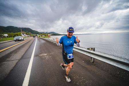CARLETON, CANADA - 4 juin 2017. Au cours du 5e Marathon de Carleton au Québec, au Canada. Happy Man Marathoner sur le bord de la route et de l'océan. Banque d'images - 82386509