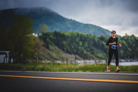 CARLETON, CANADA - 4 juin 2017. Au cours du 5e Marathon de Carleton au Québec, au Canada. Jeune femme Marathoner à environ 7 km de distance Seul sur le coté de la route et de l'océan Banque d'images - 82386515
