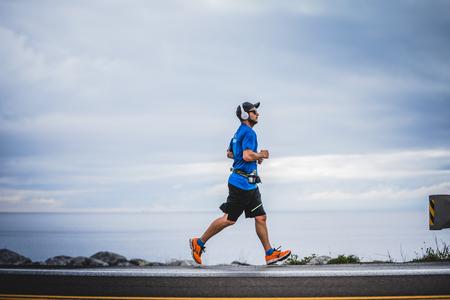 CARLETON, CANADA - 4 juin 2017. Au cours du 5e Marathon de Carleton au Québec, au Canada. Young Man Marathoner à environ 7 km de distance Seul sur le coté de la route et de l'océan Banque d'images - 82386522