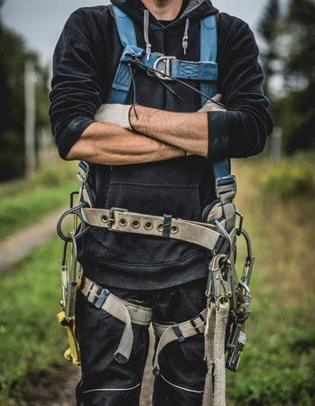 Crop unrecognizable technician in uniform with harness standing with arms crossed. Archivio Fotografico