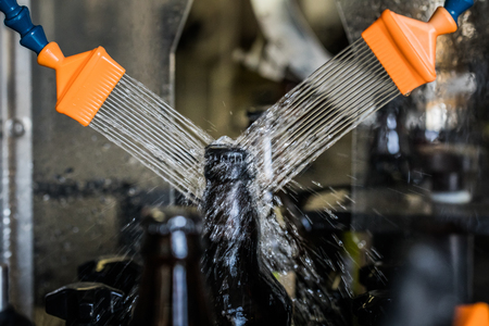 Brown glass 500ml beer bottles washed with water on conveyor on microbrewery.