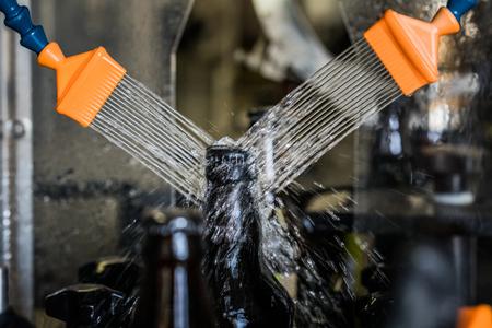 Garrafas de cerveja de 500 ml de vidro marrom lavadas com água no transportador na microcervejaria. Foto de archivo - 92088179
