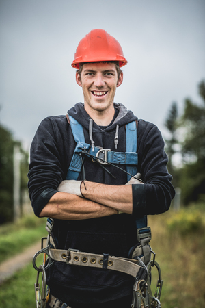Cheerful technician man in uniform with harness standing at telecommunication tower