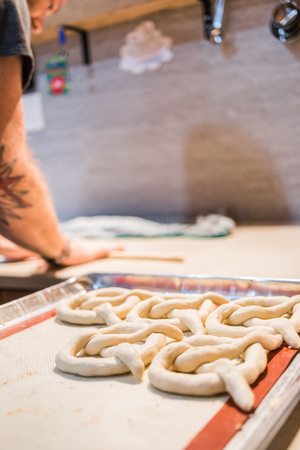 Crop unrecognizable person preparing and forming pretzels before cooking.