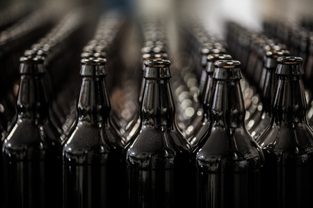 Rows of empty brown glass bottles prepared for filling on factory.