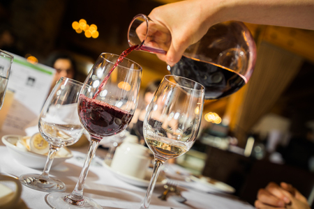 Hand of unrecognizable waiter pouring red wine to glass in restaurant.