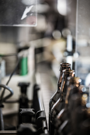 Dark brown glass beer bottles prepared for filling and bottling on conveyor of microbrewery.