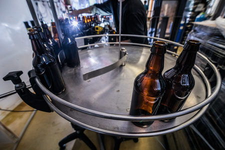 Brown glass beer bottles on conveyor for filling and bottling.
