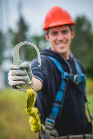 Dafety First ! Smiling technician man in hardhat showing safety hook on rope.