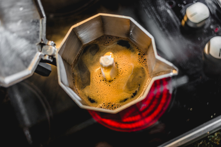Italian Aluminum Coffee Maker in Action Brewing a Fresh Dark Coffee on the Stove