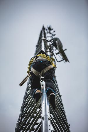 도구 및 하네스로 안테나 탑을 등반하는 통신 노동자 스톡 콘텐츠