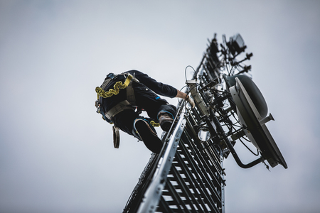 Telecom Worker Climbing Antenna Tower with Tools and Harness Stock fotó - 92242362