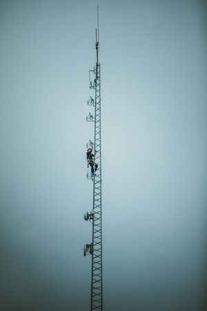 Telecom Worker Climbing Antenna Tower with Harness and Tools