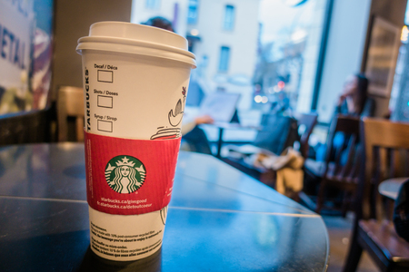 Montreal, Canada _ December 1, 2017. Starbucks Coffee Cup on a Table with Blurred People in Background.